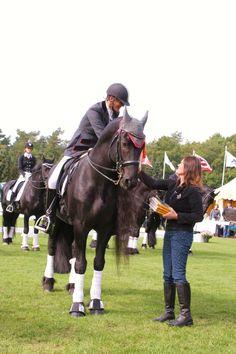Christine Linneweever overhandigt het allernieuwste deel uit de serie Gouden Paarden, De redding van Roan aan de winnaars van de dressuurkampioenschappen voor het friese paard