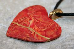 Broken heart pendant in a swirled mix of red, orange, and yellow polymer clay with gold kintsugi (or kintsuguroi) style repair - OOAK by AKintsugiLife