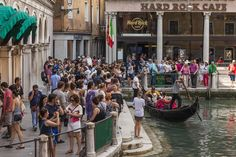 Tourist are seen taking picture of Gondolier and waiting for their turn for a ride on a gondola next to the Hard Rock Caffe in Bacino Orseolo on July 3, 2015 in Venice, Italy.