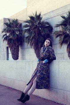 Model Anisia Khurmatulina wears brocade Miu Miu coat, dress and boots with Blumarine belt