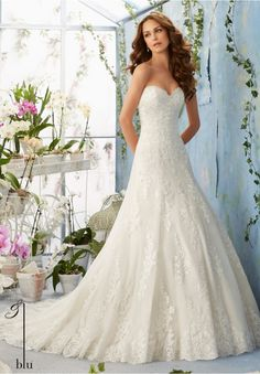 """Wedding Gowns By Blu featuring Embroidered Lace Appliques Decorate the Net Gown with Scalloped Hemline Over Soft Satin Available in Three Lengths: 55"""", 58"""", 61"""". Colors available: White, Ivory, Ivory/Coco."""