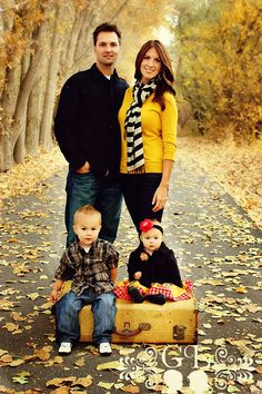 LOVE this family photo idea - Love how it's outside in nature in the bright colored leaves & I love their choice in clothing & I love the props!  :)
