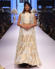 White lengha and bustier top with golden flower pot prints. Matching floor length sleeveless sheer jacket with embroidered detailing.Disclaimer: There might be a slight color variation in this item as this image is from the actual runway show.Wash care: Dry clean onlyCap worn by the model is only for styling purpose