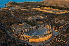 Leptis Magna, una de las ciudades romanas más grandes y mejor conservadas del mundo, floreció bajo el emperador Septimio Severo, oriundo del lugar. Su gran teatro, el foro (arriba, a la derecha) y el mercado formaban parte de un centro urbano que llegó a rivalizar con Roma. Gadafi veía en estas ruinas un símbolo del imperialismo occidental.