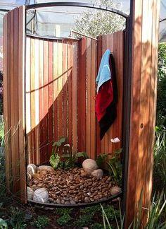 Elliptical Outdoor Shower - Zu dreiviertel mit Holz umschlossene Außendusche, abgerundete Steine als Untergrund auch für die Gartenduschen von www.Wellness-Stock.de bestens geeignet