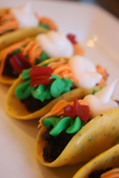 """Candy """"Tacos""""; Shells made out of candy melts and crushed up oreos, """"meat"""" is brownie, """"lettuce, cheese and sour cream"""" is buttercream and """"tomatoes"""" are twizzlers."""