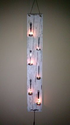 Fun spoon candle holder. Made from old plank of wood that has been painted and weathered, we bent 6 Goodwill spoons and screwed them into the wood.  We used a thick piece of hemp to hang from the wall and placed a bracket at the bottom with a long baby spoon to act as a snuffer.