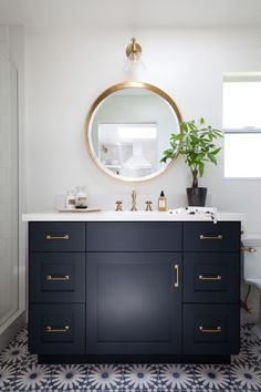Gorgeous bathroom floor tile! A black vanity with brass hardware and matching mirror complete this elegant look.