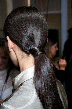 The low ponytail is an old standby, but this one takes things one step further. Once you secure your hair into a low pony, take a two-inch s...