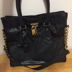 Authentic Michael Kors black tote Very gently used and in excellent condition. This was purchased before MK's huge expansion, so the leather (and overall) quality is significantly and noticeably better. Black leather. Authentic. 24K gold plated hardware. Dust bag included. Minor wearing of the gold plating at the lock (see image 3), but it's only slightly visible up close. Michael Kors Bags