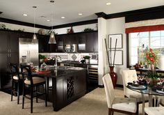 High contrast white walls and dark stained wood design in this open kitchen visually separate the space from dining area.