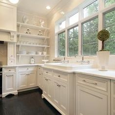No Upper Cabinets - kitchen shelves. Full bank of windows on the outer wall. Apron sink. white cabinets.