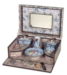 """10"""" x 6"""". A wooden box with decorative paper covers and engraving card """"Service Toilette"""" on the lid hinges open to reveal mirrored back and well-fitted interior,comprising porcelain wash bowl and pitcher,two lidded boxes,small bowl,two puffs,soap,perfume bottle and comb. Excellent condition of the luxury doll accessory. French,circa 1885."""