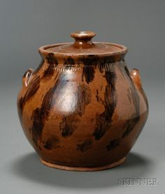 Redware Covered Bean Pot, probably New England, early 19th century, bulbous form with rouletted neck, decorated with spiraled splotches of brown manganese, (minor glaze wear), ht. 9 in.     minor glaze wear around cover rim, rim and handle edges, light surface wear around middle, base edge good.   Sold for $ 3,555