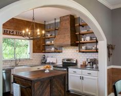 Jo's redesign incorporated lots of different materials to add plenty of character: stone countertops, a wood island, shiplap walls, subway tileand shelving made from plumbing pipes. She even had Chip carve out an archway to lead from the kitchen to the dining area.