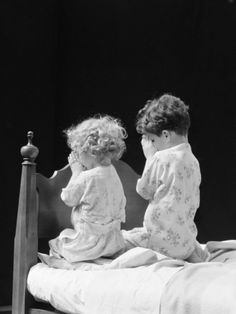 H. Armstrong Roberts - Boy and girl kneeling by bed praying, USA  ca. 1930's. °