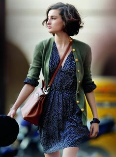 Green cardigan with large gold buttons and sleeves rolled up. Blue dress with half sleeves. Brown purse.