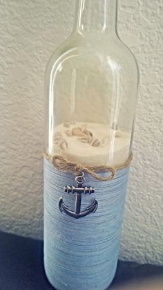 Up-cycled decorated wine bottled with a nautical theme filled with white sand, tiny sea shells wrapped in a sky blue thread sealed with a cork and embellished with a metal anchor and jute. A great decorator piece. Additional shells included as some settling may occur during shipping. Smart Hippie happily accepts custom orders. Large orders for parites and centerpieces are appreciated and will be handmade with pride.