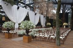 Cerimônia de casamento na Hipica Santo amaro com cortinas de voil brancas, arranjos de flores brancas, cadeiras e detalhes em madeira e passadeira nude.