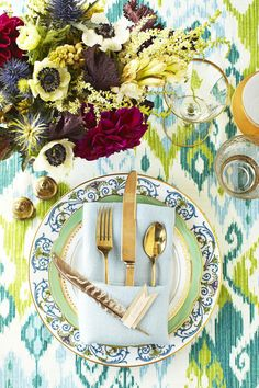 Gilded flatware and vintage plates look especially pretty on top of elaborate linens in a floral or paisley pattern. Click through to see more of the best Thanksgiving table setting ideas! #thanksgivingplacesettings #thanksgivingtablesettingssimple #thanksgivingplacesettingsdiy #easythanksgivingplacesettings