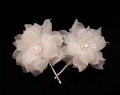 El tocado de Novia de flor de rosa de Duo es artesanales dos flores seda puras con cristales de Swarovski y perlas de agua dulce. Pétalos de flores son hechos a mano con 100% de seda. Son corte de mano, mano presiona y mano reunidos uno por uno por métodos de sombrerería. El centro de cada flor de seda pura está adornado con grandes racimos de cristales de Swarovski y perlas de agua dulce. El tocado de novia mide aprox. 4.5 3,75. Opciones de color de los pétalos son marfil y blanco. Las dos…