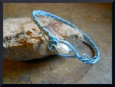 """Baby Blue Wire Bracelet    7 1/2"""" baby blue artistic wire bracelet. This wire is satiny smooth and is such a delicate design.  The closure is a fresh water pearl. The colors together are simply elegant."""