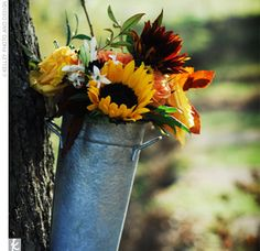 Galvanized pails filled with sunflowers and other autumnal blooms hung in the trees surrounding the ceremony. In true Kansas spirit, Theresa requested sunflowers for many of the wedding day arrangements.