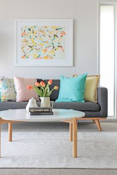 Bright colourful lounge room grey sofa round coffee table