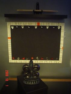 Recycled bulletin board painted black with sheet music decoupaged on. Used guitar picks as tacks for tickets, posters, etc..