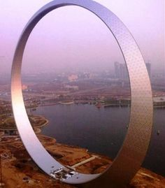 """The enormous monument """"Ring of Life"""" in Fushun, Liaoning Province in China, a 515-foot (157 meters) high metal structure, serving as an elevated sighting site. Ring of Life a monument like the Eiffel Tower, made of 3,000 tons of steel, uses four elevators to take people to the top and will glow at night by 12,000 LED lights."""