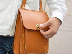 本体底面がラウンドしており、かぶせの上部が縫い付けられているユニークな作り。留め具も丸大おこしと特徴的なポシェットです。文庫本とお財布と携帯を入れて、お散歩にどうぞ。