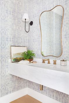 Eskayel wallpaper brightens up the powder room, which boasts a vintage mirror and sleek Urban Electric Co. sconces.