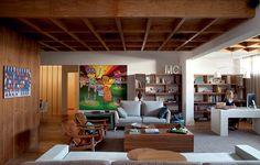 Para a sala ficar bem acolhedora, a arquiteta Fabiana Avanzi caprichou na madeira. Com home office integrado, ela recebeu assoalho de peroba e forro de pínus. O quadro dos grafiteiros Osgemeos mostra a paixão dos moradores por arte contemporânea