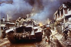 Vietnamese Rangers move up a street in Cholon as another part of the Chinese section of Saigon burns on May 9, 1968