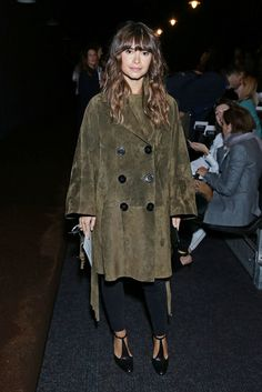 Miroslava Duma wears a suede peacoat, black pants, and t-strap heels