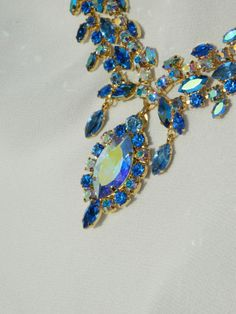 (close up of necklace piece) Vintage red carpet elegance with a grand parure featuring all Swarovski crystal. Stones are vintage sapphire aurora borealis and current-market aurora borealis crystals intermixed to create an ocean of glittering blue.....gold plated