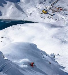 Man skis in Portillo, Chile, with yellow Grand Hotel Portillo in background