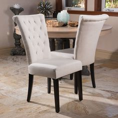 Add sophistication and comfort to your living space with a set of Evelyn tufted wing back hostess chairs. These thickly padded, button-tufted back seats are fully upholstered with a natural stain fini