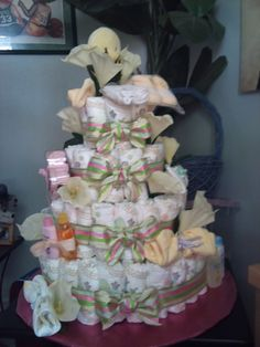 "DIY diaper cake! diapers, rubber bands, 1/4"" poster board + ribbon and embellishments! That's it!"
