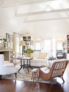 Fresh white living room. Interesting free standing taller table that can be moved around in place of a traditional coffee table.