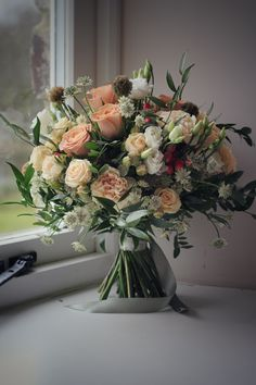 Cream and beige wedding bouquet. Cappuccino roses, astrantia, seedheads, berries.