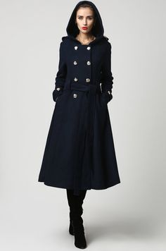 This beautiful long wool coat features a double-breasted bodice and oversized silver buttons to create a distinct but classic military style. It features gorgeous navy blue wool, a polyester lining, and fun features like extra long sleeves, deep side pockets and back split vents. The self-tie belt makes it easy to accentuate your waist while the warm hood will stylishly shield you from the cold.  DESIGN FEATURES  *Wool Blend *Super Soft Wool fabric *Polyester Lining *Cozy Warm Hood *Self-Tie…
