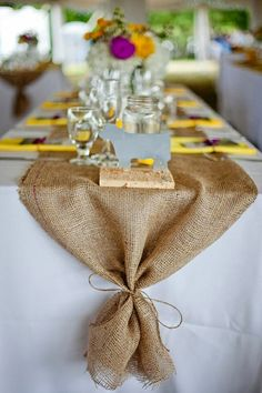 Similar linen choices except round 60 inch tables with criss crossing burlap runners and yellow napkins.