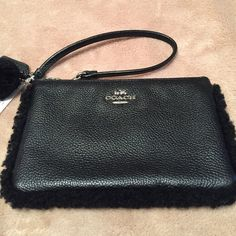 """Coach Shearling Zip Black Leather Wristlet. NWT Plush Black Pebbled Leather with shearling trim and a cute Pom Pom. This Coach Wristlet is large enough to hold your phone, lipstick, ID, cash, credit cards, and up to an IPhone 6. Approximate Measurements: 7"""" L X 4-1/4"""" H Coach Bags Clutches & Wristlets"""