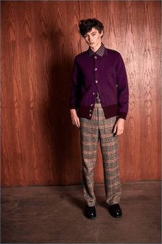 Smart style is front and center with a cardigan, printed shirt, and check trousers by Orley.