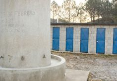 A close up of the hand washing station with latrines in the background.