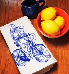 Set of four dinner napkins that are washable and reusable. These are bright white cloth dinner napkins featuring an image of a blue fish on a bicycle. I personally hand draw all of my designs and hand pull all of my screen print images. The printed cotton table napkin are eco-friendly