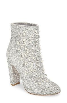 Polished beads and twinkly crystals add sparkly dimension to a statement glitter bootie lifted by a half-moon block heel.
