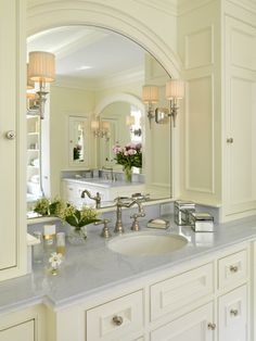 Marble counters, arched mirror, sconces with pleated shades, silver hardware, lilly of the valley arrangement - Jan Gleysteen Architects, Boston