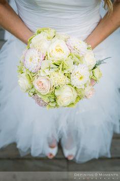Bruidsboeket in zachte wit, crème en groene pasteltinten met crèmekleurige rozen, zachtgroene hortensia en witte dahlia.